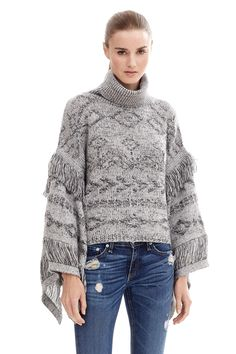 Textured knit turtleneck sweater is designed with an allover tribal print and trendy fringe detailing on the sleeves. Flowy poncho silhouette. Ribbed trim. Relaxed. Fabric: 70% rayon 30% poly. Fit: True to size. Model is wearing size small.