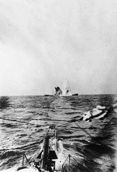 A surfaced U-Boat torpedoes a merchant steamer