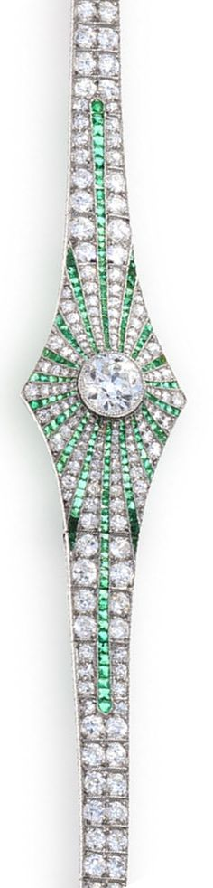 An art deco diamond and emerald bracelet, circa 1925  centering an old European-cut diamond within a radiating surround of calibré-cut emeralds and single-cut diamonds, completed by a tapered bracelet; with French import marks; central diamond weighing approximately: 1.25 carats; remaining diamonds weighing approximately: 4.80 carats total; mounted in platinum; length: 6 1/4in.