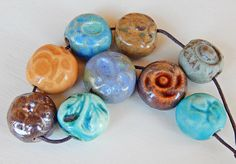 Set beads , mix colors . The set consists of 9 porcelain and stoneware beads ,they are carved by hand and have several green , ocher , blue , turquoise and brown glazes . By Mª Carmen rodriguez ( Majoyoal ) https://www.facebook.com/groups/CeramicArtBeadMarket