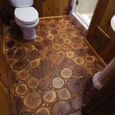 Chicago flooring company Birger Juell Ltd., created this bathroom floor of horizontal cuts of oak, birch, and maple, as well as tiny twigs and branches gathered from the client's property. DIY Flooring - Bob Vila | Tiny Homes