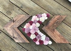 3 set Chevron Arrows stained honey brown with one arrow decorated in Blush pink, burgundy, cream, and dusty purple sola flowers. Arrow measures 14x 14 from farthest tips. Flower covered arrow measures 14x15 from farthest tips. 6 command strips included to hang the arrows.