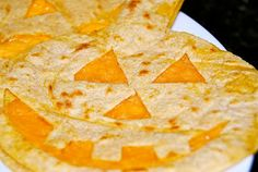 """Halloween Quesadillas """"Using my kitchen shears I trimmed up 2 corn tortillas to include stem and then using a sharp knife I cut out a face on one of them. I next just toasted the pumpkin without a face and topped it with cheese, toasted the face one and covered the cheesy face. They were easy and cute."""""""