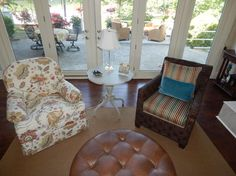 A Balta chairs and a Devonshire swivel glider chair with a Leah Spiral Pedestal Table between them and a Leather Nassau ottoman in-front. By: Andrea Ciano Aciano@pineville.ethanallen.com Photo Credit: Andrea Ciano