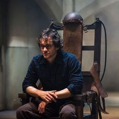 Hugh Dancy in a reflective moment sits in the electric chair.