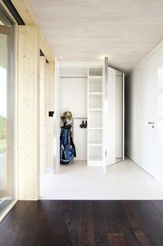 Showing Woodne Storage Beside the Flower and Shoes Hanging that Dark Flooring Added Cool the Room