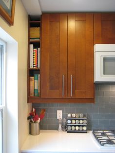 Extra space = storage for cookbooks or wine.  Love the cabinet color and handles