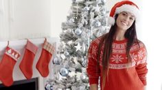 Pretty young woman celebrating Christmas at home posing in front of the decorated tree in a festive red sweater and Santa hat - HD stock video clip
