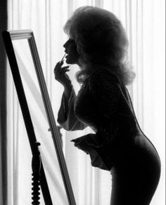1976- Dolly Parton Nashville, Tennessee. photographed by Harry Benson.  a black and white photograph of infamous Country Music singer, Dolly Parton's silhouette while she was doing her make-up. the higher the hair, the closer to god.
