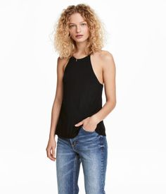 Black. Gently flared camisole top in jersey with a sheen. Narrow shoulder straps crossed at back and lined upper section.