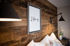 Instead of a headboard behind the master bed, a reclaimed wood wall creates the focal point in this rustic, industrial space. In the center of the wall, the artwork, printed from Etsy and outlined in a rustic frame, adds a personalized touch to the couple's master sanctuary and reminds them of their forever love.