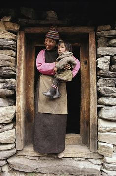 Smiling Bhutanese Woman And Child at The Doorway