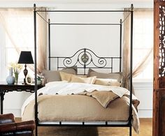 Alexandria Canopy Bed  Authentic 19th Century European canopy bed design with intricate centerpiece cast in solid brass. Heavy solid brass pineapple finials crown the bed posts. Scrollwork and rope details on the panel are hand forged iron.