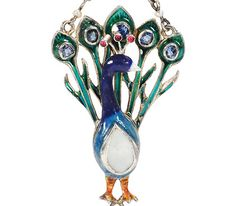 Art Deco Proud as a Peacock Pendant - The Three Graces - In the center of his belly is a teardrop of mother of pearl rimmed in silver. From his shimmering silver back a train of five green enamel feathers is dotted with five (5) blue sapphire eyes. Atop his head sprouts a silvery crest set with three red paste stones. An enamel bale suspends two lengths of chain attached to the ends of his fan-like tail while a small baroque pearl drop is clutched by his orange feet.