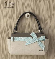 Riley    At first glance, the gorgeous color of the Riley for Classic Bags might just remind you of a sweet caramel macchiato—with an extra splash of vanilla! Riley features unusual jute fabric in light tan with an unexpected sparkle of silver threading throughout. Taupe faux patent leather belt loops as well as top and end pockets detail. Includes charming soft blue fabric bow with white cherry blossom print.    https://purse-divas.miche.com/Shop/Product/1194