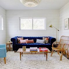 Love the mix of styles and textures in this mid-century living room, from the Moroccan diamond patterned rug to the wicker arm chair to the rich blue Chesterfield sofa.