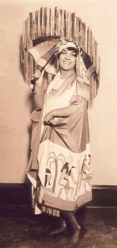c. 1920s photograph of an elaborate and no doubt colorful ensemble, complete with fringed parasol.  Back of photo stamped 'Keystone View Co. Inc. of N.Y.' and has a piece of paper affixed with a typewritten caption: 'Bathing Suits For the Sunny South – Egypt is not forgotten these days.  Here is Claire Cassel, noted tennis star, in a stunning costume, especially designed for her by Miss Elsie Hiller.  Miss Cassel is due south where she will show these bathing suits to Palm Beach.'