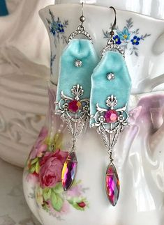 I hung aqua velvet ribbons from rhinestone rings and added rhinestone montees, silver plated filigree findings and faceted glass briolette beads to create these fun yet elegant earrings. Lightweight, approximately 4 inches from the top of their silver plated French ear wires and