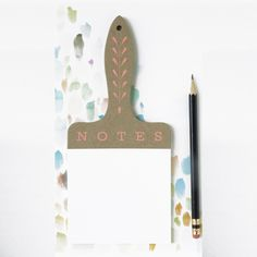 "A die cut notepad in the shape of a life size paintbrush with neon pink screen printed design that references carvings found on vintage tools.  Details: 8""x 3.5"" Pages are perforated at the top."