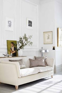 Love the picture wall and cream sofa in this white panelled living room.