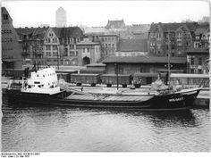 """http://www.app-in-die-geschichte.de/document/50806 Zentralbild Löwe 23.5.1957 Ho.- Reger Betrieb im Hafen von Rostock. Das Küstenmotorschiff der Deutschen Seereederei """"Wolgast"""" am Kai."""