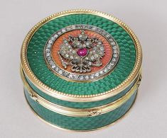 Fabergé Peter Karl 1846 1920 Entwurf A redgold box with enamel ornament 20th cent. 14 ct. red and yellow gold. Marked '56' with Moscow town mark. Marks 'Fabergé' and 'HW'. Green and red enamel with applied eagle ornament and rose cut diam. and ruby red stone. H. 25,5 cm. Diameter 49,5 cm.