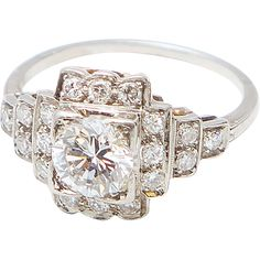 The unique architectural details of this fabulous Art Deco diamond ring display all the elements specific to that era. The star of this drama is an