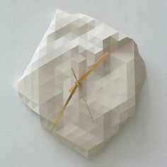 """These faceted wall clocks are individually cast in a natural white resin and are formed in a flexible mould which is manipulated by hand for each piece to give every clock a unique shape, so no two are the same. The clock measures approximately 12"""" across at its widest point and is available with Gold, Black, or Silver hands. Each clock is hand built in the Birmingham, UK studio of Raw Dezign. Made to order. Please allow four weeks for shipping."""