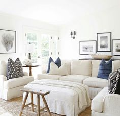 Modern beach house style in a living room design featuring black and white artwork, white linen slipcovered sofa, chairs, and ottoman, pillows in indigo blue and black and white woven patterns, a rustic wood bench, and seagrass area rug - Neutral Home Decor & Decorating Ideas - fragments identity.com