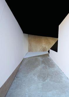 black ceiling + white walls + concrete floor + angles