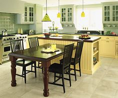 I think the appeal of this design comes down to a pretty simple idea: yellow flat-panel base cabinets paired with soft green upper cabinets with divided lights. A dark teak T-shaped island and black granite countertops tie the cheerful, soft colors together and give them a sophisticated edge.