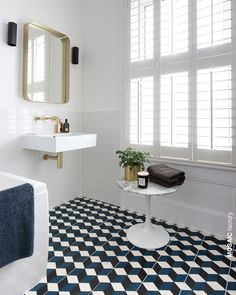 All white bathroom with contrasting patterned floor tiles in blue, white and black. The geometric cubic tile pattern is from Mosaic Factory CEMENT TILE collection. Buy online from stock or customise your own colourway! Design by / photo: Cathy Pyle White Bathroom Tiles, Bathroom Floor Tiles, Small Bathroom, Tile Floor, Brass Bathroom, Brass Mirror, Black And White Bathroom Floor, White Bathrooms, Industrial Bathroom