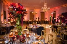 Red lighting with gold and grape colored table setting and read flowers.  Includes gold versaille chairs.