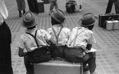 Three boys sitting on a suitcase.