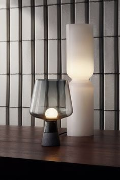 Designer Magnus Pettersen used the inspiration of glass and concrete in modern architecture to create the Leimu table lamp. The combination of the mouth blown glass 'shade' and the concrete base creates a streamlined design that emphasizes the beauty of both materials. Leimu brings an elegant point of interest to any space.  The Lantern lamp reflects a soft, flickering glow that creates relaxed ambience. The versatile light fixture fits easily in many places from shelves to open spaces.