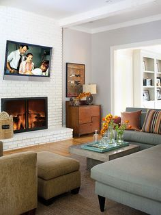 Straight-lined furniture and a cool color palette give this living room contemporary appeal. To update the traditional-look brick fireplace surround, the homeowners gave it a fresh coat of crisp white paint. Now, the fireplace surround incorporates texture without distracting from the room's clean-lined aesthetic.