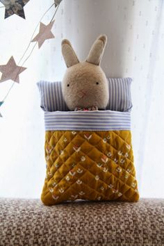 homemade stitched  tiny toy rabbit in a bed.