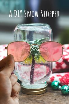 Shake things up this season. Have an extra-hipster holiday when you add the arts and crafts to Christmas with a tropical-themed mason jar snow globe. Then, add an extra dash of new with modern flat lenses on the Hexagonal sunglasses from Ray-Ban.