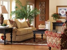 Three ornamental and ornate art installations hang on a brown wall in this traditional living room that includes a cream-colored sofa, red patterned and neutral striped pillows, a red and gold armchair, brown coffee table, sideboard, and end table.  Red accents in the floral arrangement and floral artwork compliment the color scheme of the room.
