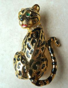 This is a lovely vintage enamel and rhinestone collared leopard brooch. The brooch design is of a leopard with his back to you, tail up high and the head turned to face you. It has green rhinestone eyes and clear rhinestones set in its collar with black enamel detailing and a touch of red enamel to the mouth, set in gold tone metal.  The brooch is marked to the back with the manufacturers number A266 Vintage circa 1980's
