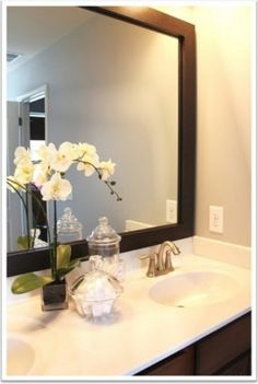 Build a wood border around current mirror in all bathrooms