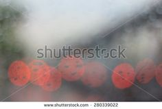 Blurred rainy window with red bokeh light
