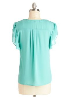 Make a refreshing fashion statement when you don this semi-sheer aqua top! Created from smooth chiffon-like fabric, this collarless button up invigorates you with cool design details, such a V-neck collar, slight intermission hemline, and short flutter sleeves. Proclaim your style in this cool-colored blouse!