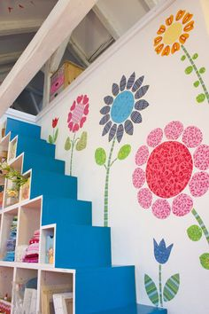 cute idea for a craft or girl's room. fabric cutouts and staggered shelving