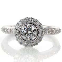 Lovely modern diamond engagement ring has a round center stone bezel set and surrounded by a halo. The band and halo are both done in micro pave. Design 1718 from Knox Jewelers
