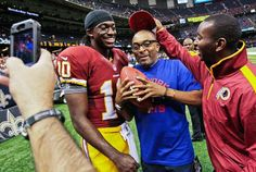 Washington Redskins quarterback Robert Griffin III (10) poses for a photo with director Spike Lee, center, after a game against the New Orleans Saints at the Mercedes-Benz Superdome in New Orleans Sept. 9, 2012. (Matthew Hinton/AP)