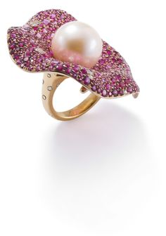An amazing cultured pearl, red spinel and diamond 'Parabola' ring. Designed as a lily pad, the coiled shank set with brilliant-cut diamonds, to the central cultured freshwater pearl, accented by pavé-set red and pink circular-cut spinels and brilliant-cut diamond highlights.
