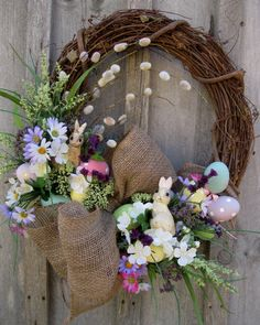 Two adorable bunnies nestled among the blooms & a lush burlap bow adds a charming country touch to this Easter wreath!