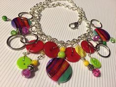 Layers of red, yellow and green buttons are combined with painted beads, silver rings and glass beads with a hint of lavender for an eclectic