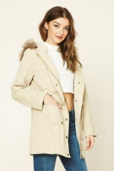 A woven utility jacket featuring a faux fur-lined hood, snap-button zip-up front, drawstring waist, faux shearling lining, two front patch pockets, and long sleeves.